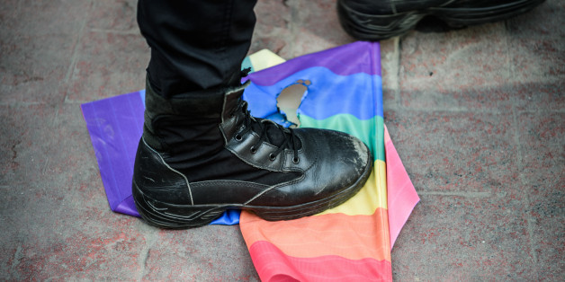 A Turkish anti-riot police officer steps on a rainbow flag during a rally staged by the LGBT community on Istiklal avenue in Istanbul on June 19, 2016.Turkish riot police fired rubber bullets and tear gas to break up a rally staged by the LGBT community in Istanbul on June 19 in defiance of a ban. Several hundred police surrounded the main Taksim Square -- where all demonstrations have been banned since 2013 -- to prevent the 'Trans Pride' event taking place during Ramadan. / AFP / OZAN KOSE