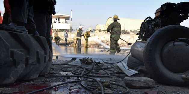TOPSHOT - Afghan firefighters wash a road at the site of a suicide car bomb near the international airport in Kabul on December 28, 2015. A Taliban bomber has detonated an explosives-packed vehicle near Kabul airport in an attack on a NATO convoy, killing one civilian a day after Pakistan's army chief visited the Afghan capital in an effort to revive peace talks.Four other civilians were wounded in the early morning attack, which comes amid a worsening security situation in Afghanistan as the Ta
