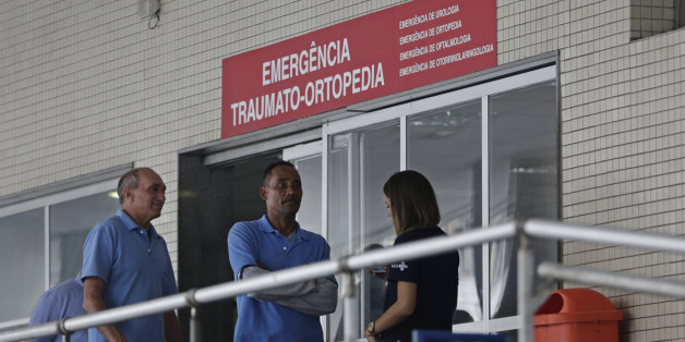 Employees stand in front an emergency entrance at the Souza Aguiar Hospital, in Rio de Janeiro, Brazil, Sunday, June 19, 2016. Brazilian police say armed men stormed the Rio de Janeiro hospital to free a suspected drug trafficker, sparking a shootout with officers, with at least one patient killed, and a nurse and an off-duty policeman wounded. (AP Photo/Silvia Izquierdo)