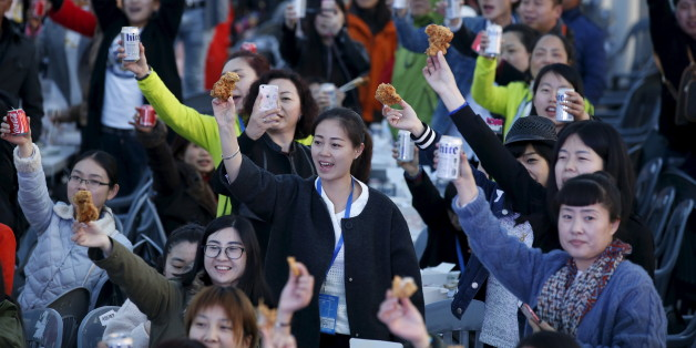 Chinese tourists make a toast with canned drinks and fried chicken pieces during an event organized by a Chinese company at a park in Incheon, South Korea, March 28, 2016. REUTERS/Kim Hong-Ji