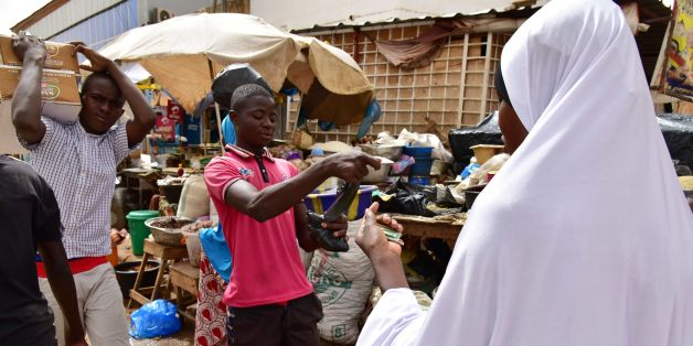 A muslim woman purchases goods for the Ramadan holiday at a market in Niamey on June 12, 2016.  The month-long Ramadan holiday is spent by Muslims fasting during the daylight hours from dawn to sunset. / AFP / ISSOUF SANOGO        (Photo credit should read ISSOUF SANOGO/AFP/Getty Images)