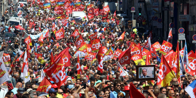 CORRECTS THE DAY. Workers hold flags and demonstrate during a day of strikes and protests, in Marseille, southern France, Tuesday, June 14, 2016. Workers strike across sectors of the French economy and march through French cities in what unions hope is a huge outpouring of discontent at changes to labor protections and a big challenge to the government. (AP Photo/Claude Paris)