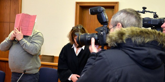 German former male nurse Niels H (L) hides his face behind a folder as he waits for the opening of another session of his trial on February 26, 2015 at court in Oldenburg, northwestern Germany. A verdict is expected in the case in which the 38-year-old nurse had admitted killing over 30 hospital patients with lethal injections in a thrill-seeking game to try to revive them.      AFP PHOTO / DPA / CARMEN JASPERSEN   +++   GERMANY OUT        (Photo credit should read CARMEN JASPERSEN/AFP/Getty Images)