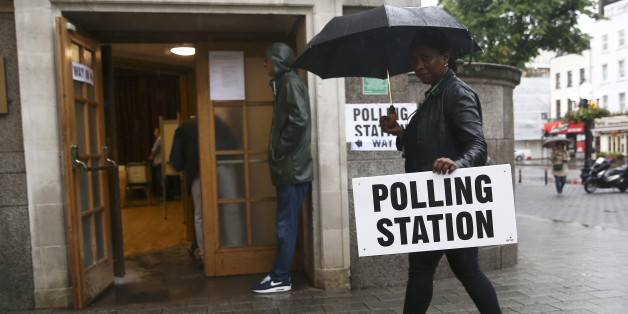 A woman carries an umbrella and a polling station sign at a polling station for the Referendum on the European Union in north London, Britain, June 23, 2016.   REUTERS/Neil Hall
