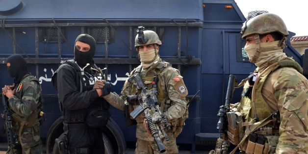 Tunisian special forces stand outside a house containing the body of a man after security forces said they killed a 'terrorist' on March 21, 2016 on the outskirts the southern border town of Ben Guerdane where jihadists mounted a deadly assault earlier this month.   The security source said the raid came as part of an operation launched on March 20, 2016 to target the alleged killer of an official in the security forces during the March 7 assault. The army and security forces have deployed around Ben Guerdane since jihadists launched a dawn assault on security installations in the area on March 7, killing 13 members of the security forces and seven civilians.     / AFP / FATHI NASRI        (Photo credit should read FATHI NASRI/AFP/Getty Images)