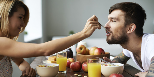 Beautiful girl feeding her boyfriend with spoon, this couple is so contemporary and cute!