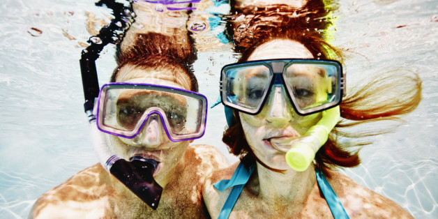 Husband and wife wearing snorkel masks underwater view