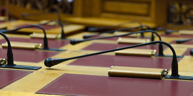 The desks and microphones inside the empty Greek Parliament