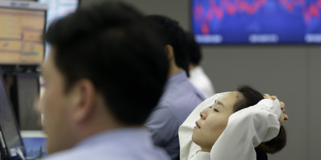 A currency trader watches her monitors at the Korea Exchange Bank headquarters in Seoul, South Korea, Friday, Jan. 16, 2015. Asian stocks were sharply lower Friday after a surprise move by the Swiss National Bank to abandon its efforts to keep its currency artificially cheap shocked the market. South Korea's Kospi fell 1.4 percent to 1,887.10. (AP Photo/Ahn Young-joon)