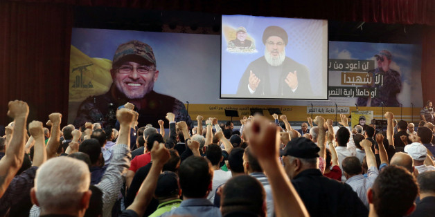 Supporters of Lebanon's Hezbollah leader Sayyed Hassan Nasrallah react as he addresses them from a screen during a ceremony marking the 40th day after Hezbollah commander Mustafa Badreddine(picture on banner) was killed in an attack in Syria, in Beirut's southern suburbs, Lebanon June 24, 2016. REUTERS/Aziz Taher