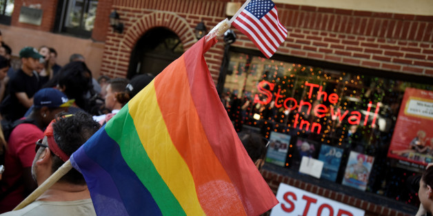 A man carries a gay pride flag at a vigil outside The Stonewall Inn on Christopher Street, considered by some as the center of New York State's gay rights movement, following the shooting massacre at Orlando's Pulse nightclub, in the Manhattan borough of New York, U.S., June 12, 2016. REUTERS/Mark Kauzlarich