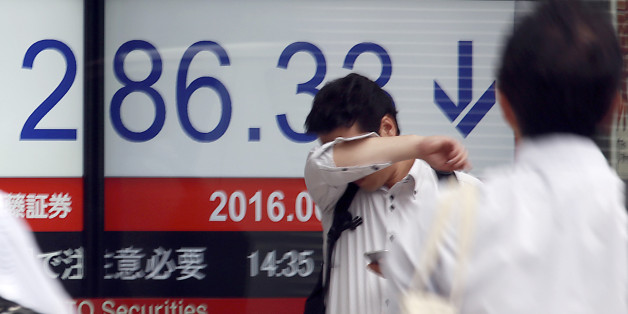 A man stands in front of an electronic stock board showing Japan's Nikkei 225 index at a securities firm in Tokyo, Friday, June 24, 2016. World financial markets were rocked Friday by Britain's vote to leave the European Union, with stock markets and oil prices crashing and the pound hitting its lowest level in three decades. (AP Photo/Eugene Hoshiko)