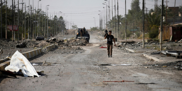 A member of Iraqi counterterrorism forces walks with his weapon in Falluja, Iraq, June 26, 2016. REUTERS/Thaier Al-Sudani