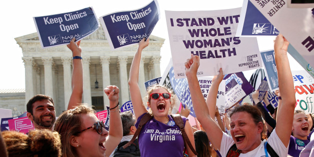 Demonstrators celebrate at the U.S. Supreme Court after the court struck down a Texas law imposing strict regulations on abortion doctors and facilities that its critics contended were specifically designed to shut down clinics in Washington June 27, 2016. REUTERS/Kevin Lamarque     TPX IMAGES OF THE DAY