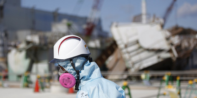 FILE - In this Feb. 10, 2016, file photo, a Tokyo Electric Power Co. (TEPCO) employee, wearing a protective suit and a mask, walks in front of the No. 1 reactor building at the tsunami-crippled Fukushima Dai-ichi nuclear power plant in Okuma, Fukushima Prefecture, northeastern Japan. Five years after a powerful earthquake and tsunami sent the nuclear power plant in the country into multiple meltdowns, cleaning up the mess both onsite and in surrounding towns remains a work in progress. (Toru Hanai/Pool Photo via AP, File)