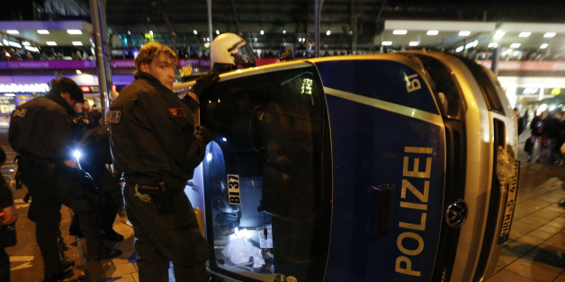 German riot police officers use torches to look for their personal belongings in an overturned police van following a demonstration by German far-right groups in Cologne October 26, 2014. The demonstration against Islamic extremism was organized by neo-Nazi groups and members of Germany's football hooligan scene. REUTERS/Wolfgang Rattay (GERMANY - Tags: CIVIL UNREST POLITICS)