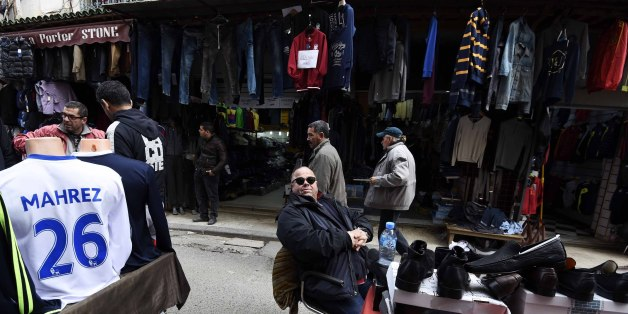 An Algerian vendor sits next to a shirt of English football club Leicester City's midfielder Riyad Mahrez displayed at a market on February 18, 2016 in the old part of the capital Algiers, known as the Casbah.   Riyad Mahrez shirts are flying off the shelves of sports shops in Algiers as the Algerian winger continues to impress for Premier League leaders Leicester City. / AFP / Farouk Batiche        (Photo credit should read FAROUK BATICHE/AFP/Getty Images)