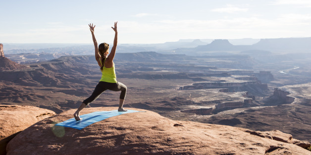 A young woman practicing yoga on top of a cliff at sunset.