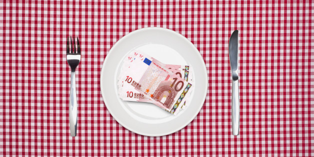 Ten Euro notes on a white dinner plate with knife and fork on a red checked tablecloth. Cost of food or restaurant concept. Overhead view.