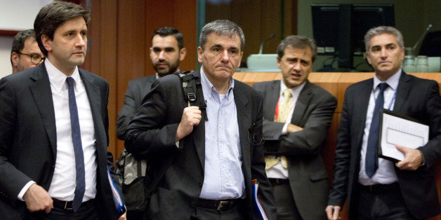 Greece's Finance Minister Euclid Tsakalotos, center, arrives for a meeting of eurogroup finance ministers at the EU Council building in Brussels on Thursday, Jan. 14, 2016. Finance ministers from the nations using the euro met in Brussels Thursday to discuss progress on Greece's economic reform program and the results of a review of measures taken by Cyprus to bring its budget into line.(AP Photo/Virginia Mayo)