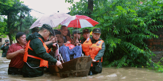 Rescuers save a resident from a flooded area in Anqing, Anhui Province, China, July 2, 2016. REUTERS/Stringer ATTENTION EDITORS - THIS IMAGE WAS PROVIDED BY A THIRD PARTY. EDITORIAL USE ONLY. CHINA OUT. NO COMMERCIAL OR EDITORIAL SALES IN CHINA.  THIS PICTURE WAS PROCESSED BY REUTERS TO ENHANCE QUALITY. AN UNPROCESSED VERSION HAS BEEN PROVIDED SEPARATELY.