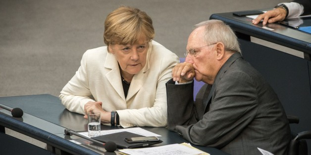 German Finance Minister Wolfgang Schaeuble (R) and German chancellor Angela Merkel attend a parliament session on the opening of a debate on next year's budget at the Bundestag (Lower House of German Parliament) in Berlin, on September 8, 2015. Finance Minister Wolfgang Schaeuble pledged to use Germany's financial firepower at hand to welcome a record influx of refugees, as hundreds more asylum-seekers arrived overnight at the key southern city of Munich. AFP PHOTO / DPA / MICHAEL KAPPELER  GERMANY OUT        (Photo credit should read MICHAEL KAPPELER/AFP/Getty Images)