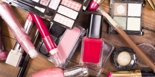 Large pile of various cosmetics lie on top of a wooden dressing table, vanity, or desk.  Make-up items include: eye shadow, nail polish, foundation, lipstick, make-up brushes,  blush, mascara, lip gloss.  Make-up artists' tools.  Great background.