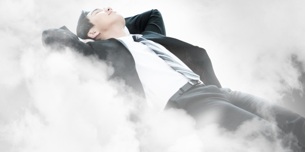 Businessman laying on the clouds