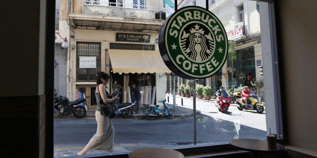 A pedestrian and scooter riders pass the window of a Starbucks Corp. coffee shop in Athens, Greece, on Wednesday, June 20, 2012. All three party leaders have committed to forming a government that will keep Greece in the euro area and fight to change some austerity measures that have led the country into a fifth straight year of recession. Photographer: Chris Ratcliffe/Bloomberg via Getty Images
