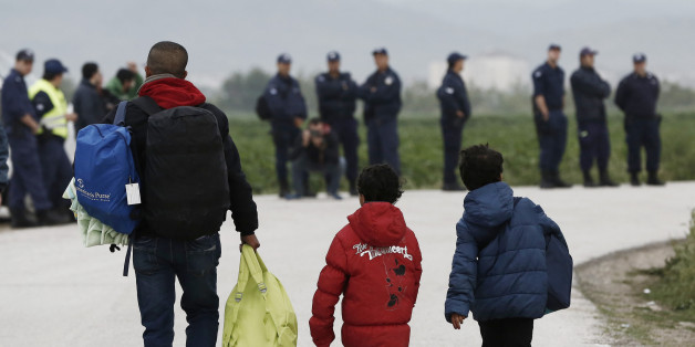 A migrant and children carry their belongings during an evacuation operation by police forces of a makeshift migrant camp at the border at the Greek-Macedonian border near the village of Idomeni, on May 24, 2016. In an operation which began shortly after sunrise on May 24, hundreds of Greek police began evacuating the sprawling camp which is currently home to 8,400 refugees and migrants, among them many families with children, an AFP correspondent said. At its height, there were more than 12,000
