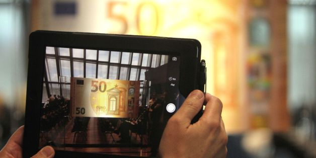 A man takes apicture with atablet computer of the new 50 EURO banknote presented at the European Central Bank, ECB in Frankfurt/Main, Germany, on July 5, 2016. / AFP / DANIEL ROLAND        (Photo credit should read DANIEL ROLAND/AFP/Getty Images)