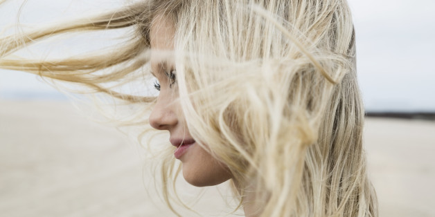 Wind blowing blonde hair of woman at beach