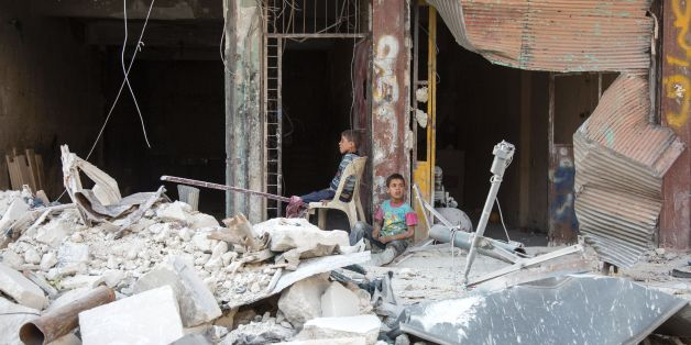 Syrian children sit amidst the rubble of destroyed buildings on July 6, 2016 in the rebel-held district of Tariq al-Bab of the northern city of Aleppo.The Syrian army said it was observing a 72-hour ceasefire across the country coinciding with the festival marking the end of the Islamic holy month of Ramadan. As fighting continued on the ground, especially in second city Aleppo, some rebel groups said they would respect the ceasefire although they doubted the seriousness of the regime of Preside