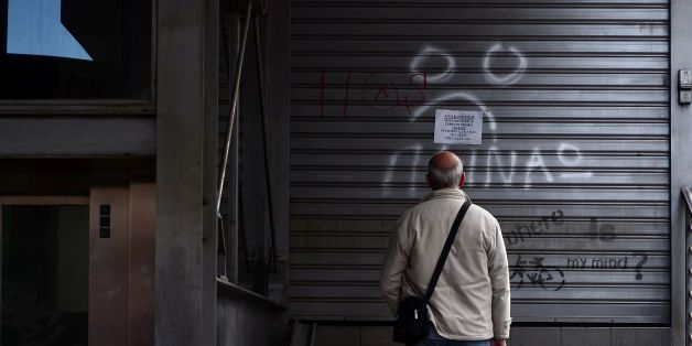 A man reads an announcement while a writing reads 'I m hungry' at a closed urban railway station in Athens, on May 6, 2016, during a 48-hours public transport strike.   Greece's labour unions stage a two-day general strike to protest against controversial government plans to overhaul pensions and increase taxes to meet demands of its bailout creditors.   / AFP / LOUISA GOULIAMAKI        (Photo credit should read LOUISA GOULIAMAKI/AFP/Getty Images)