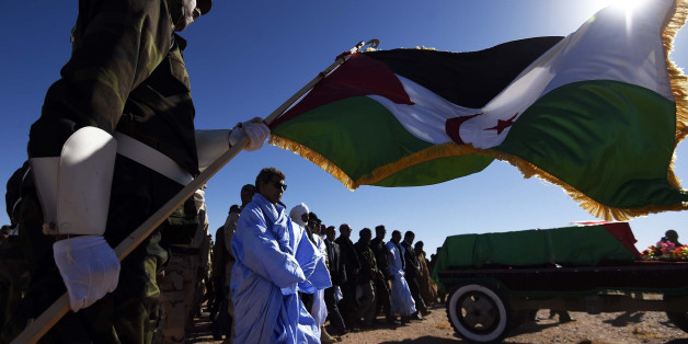 A member of the Sahrawi People's Liberation Army holds a flag of the disputed territory of Western Sahara during the funeral of Polisario Front's secretary general, Mohamed Abdelaziz, on June 4, 2016 in Bir Lahlou, some 220 kilometres (137 miles) southwest of the Algerian town of Tindouf.Abdelaziz, who was in his late 60s, had led the Algeria-backed Polisario since 1976, three years after the group was founded to struggle for independence for the territory, which was annexed by Morocco in 1975.