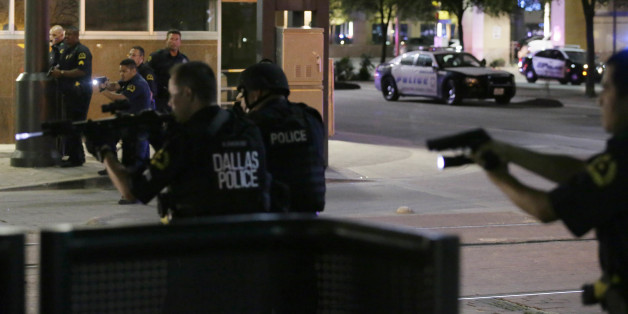 Dallas police move to detain a driver after several police officers were shot in downtown Dallas, Thursday, July 7, 2016. At least two snipers opened fire on police officers during protests Thursday night; some of the officers were killed, police said. (AP Photo/LM Otero)