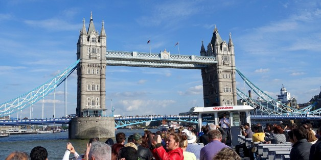 In this May 21, 2015 photo, a London City Cruises boat tours the River Thames near the Tower Bridge in London. There's plenty of sights to see for families on vacation in London, like the Harry Potter studio tour, Big Ben and the London Eye. (AP Photo/Ross D. Franklin)