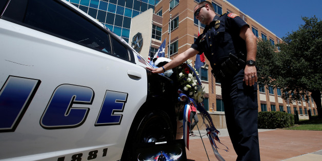 An officer touches a police car during a personal moment of silence at a makeshift memorial at Police Headquarters following the multiple police shooting in Dallas, Texas, U.S.,July 8, 2016.  REUTERS/Carlo Allegri