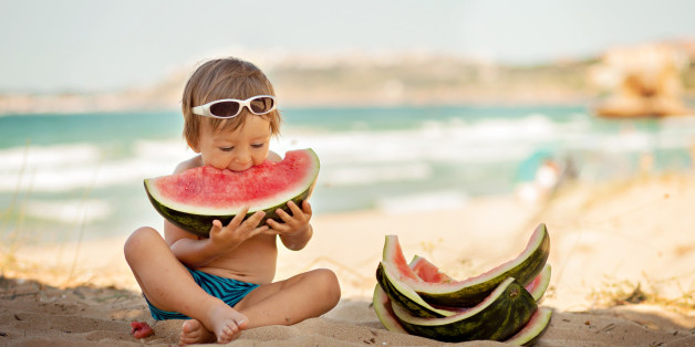 Boy eating piece of watermelon on the beach.
