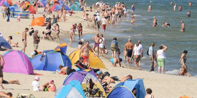 Touristen nutzen das hochsommerliche Wetter am Strand im Seebad Zinnowitz auf der Insel Usedom zum Baden und Sonnen.