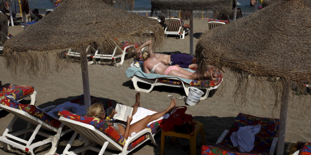 Tourists sunbathe on a beach in Fuengirola, on Costa del Sol, southern Spain, July 12, 2015. The Spanish government raised the terror-alert level to 4, out of a maximum of 5, after the attacks in France, Tunisia and Kuwait, Spain's Interior Minister Jorge Fernandez Diaz announced on June 26. Picture taken July 12, 2015. REUTERS/Jon Nazca