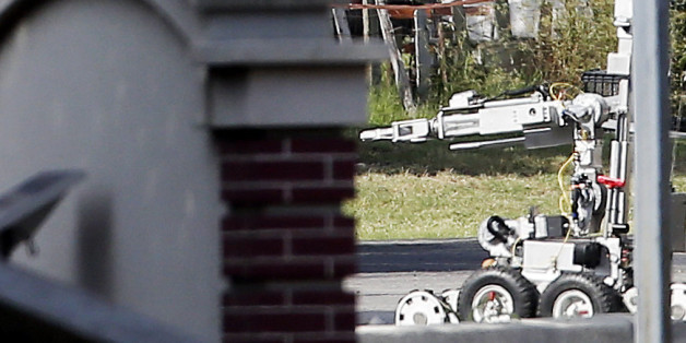 A bomb disposal robot inspects the area surrounding a armored van, top left of frame, near the intersection of Dowdy Ferry Rd and Interstate 45 during a stand off with a gunman barricaded inside the van, Saturday, June 13, 2015, in Hutchins, Texas. The gunman allegedly attacked Dallas Police Headquarters. (AP Photo/Brandon Wade)
