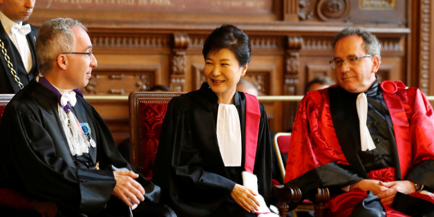 South Korean President Park Geun-hye (C) reacts after she was presented with the insignia of Doctor Honoris Causa by Francois Weil (L), rector of the Academy of Paris and Jean Chambaz (R), President of the Pierre-et-Marie-Curie University, during a ceremony at La Sorbonne university in Paris, France, June 3, 2016. REUTERS/Charles Platiau