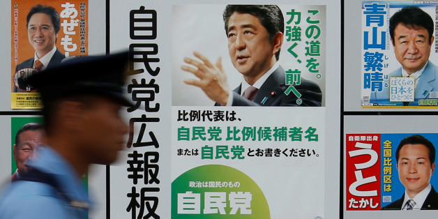 A police officer walks past Japan's ruling Liberal Democratic Party's (LDP) poster (2nd R) for the July 10 upper house election with the image of Shinzo Abe, Japan's Prime Minister and leader of the LDP, and other candidates' posters at the LDP headquarters in Tokyo, Japan July 10, 2016.    REUTERS/Toru Hanai