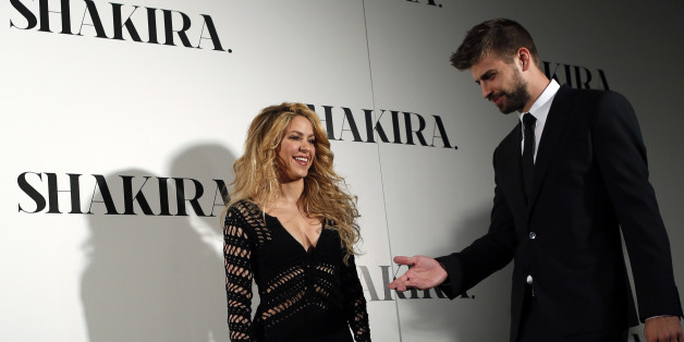 "Colombian singer Shakira and Barcelona's soccer player Gerard Pique (R) pose during a photocall presenting her new album ""Shakira"" in Barcelona March 20, 2014. REUTERS/Albert Gea (SPAIN - Tags: ENTERTAINMENT SPORT SOCCER)"