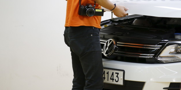 A dealer checks a Volkswagen car at a used car dealership in Seoul, South Korea, October 2, 2015. German carmaker Volkswagen , rocked by a diesel emissions scandal that erupted on Sept 18, saw its sales in South Korea slide 7.8 percent in September from a month earlier, according to industry data released on Tuesday. Picture taken October 2, 2015. REUTERS/Kim Hong-Ji