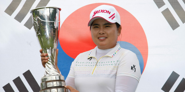 Park In-bee of South Korea holds her trophy in front of the national flag, after winning the Evian Masters women's golf tournament in Evian, eastern France, Sunday, July 29, 2012. (AP Photo/Claude Paris)
