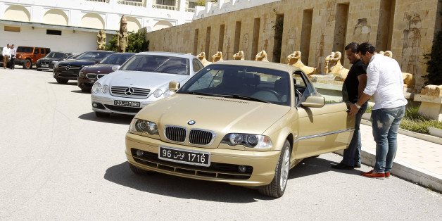 Men look at a car that once belonged to former Tunisian President Zine el-Abidine Ben Ali and his family during a public auction in Tunis May 14, 2014. Cars once owned by Ben Ali, the veteran autocrat brought down in the first Arab Spring uprising in January 2011, have been put up on auction, according to local media. REUTERS/Zoubeir Souissi (TUNISIA - Tags: TRANSPORT POLITICS SOCIETY WEALTH)