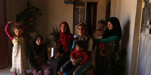 "Souad Hamidi (3rd L), 19, poses for a photograph with other members of her family inside their home, in the outskirts of Manbij, Aleppo province, Syria June 11, 2016. REUTERS/Rodi Said         SEARCH ""RODI NIQAB"" FOR THIS STORY. SEARCH ""THE WIDER IMAGE"" FOR ALL STORIES"