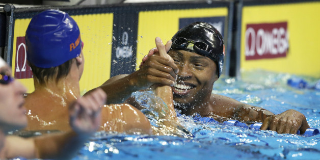 Cullen Jones, right, reacts with Caeleb Dressel, left, after their heat in the men's 50-meter freestyle preliminaries at the U.S. Olympic swimming trials, in Omaha, Neb., Friday, July 1, 2016. (AP Photo/Nati Harnik)